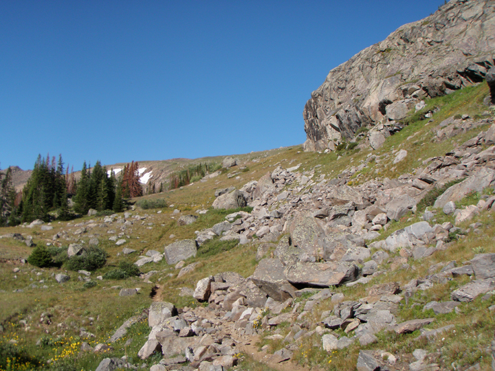 A narrow trail winds up a rocky hillside with a clear blue sky above.